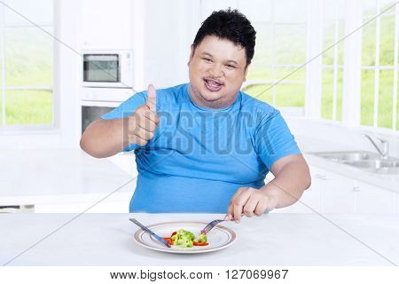 Portrait of overweight person showing thumb up while eating salad in the kitchen at home