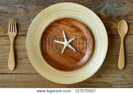 The Brown Wooden Bowl On A Rustic Table With Star Fish