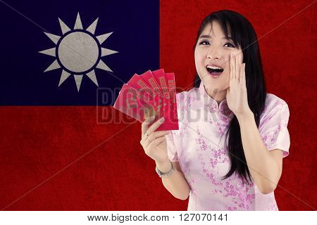 Portrait of pretty Chinese model holding red envelope and wearing cheongsam dress with flag of Taiwan