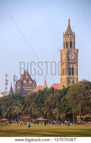 Rajabai clock tower in gothic style and green cricket field in Mumbai, Maharashtra, India