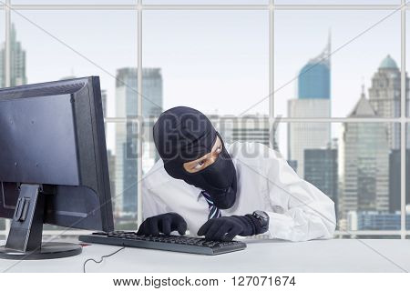Picture of watchful thief wearing mask while stealing information on the computer in office