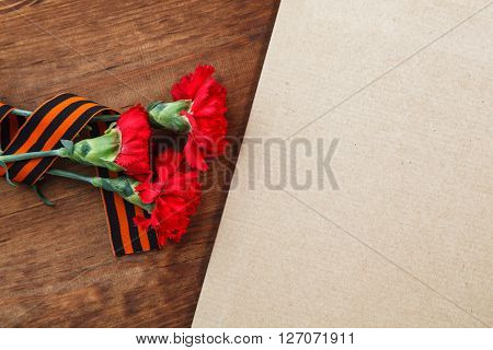 Three Red Flower And Paper On A Wooden Background. Selective Focus Image