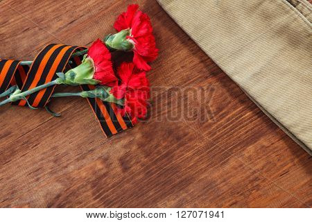 Symbols Of Victory In Great Patriotic War Three Red Flower And Soldier's Forage Cap On A Table.  Sel
