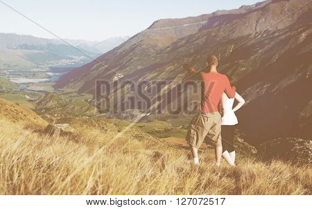 Couple looking afar where the mountain and lake are.