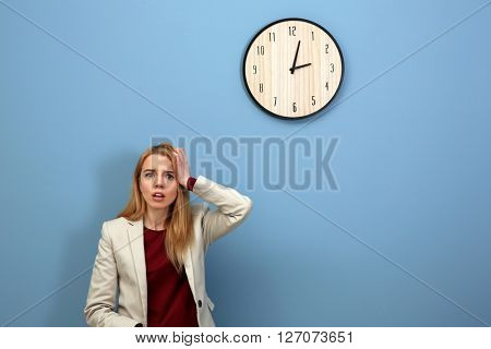 Young young beautiful woman and clock on blue wall