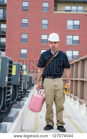 HVAC technician standing next to line of condensing units.