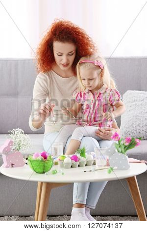 Mother and daughter decorating Easter eggs, indoors