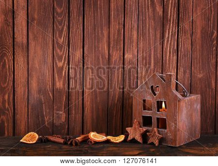 Brown house with candle and spices on wooden background