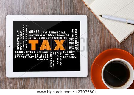 Tax concept. Tablet with cup of coffee and notepad on wooden table