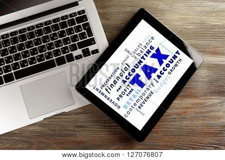 Tax concept. Silver laptop and modern tablet on the wooden background