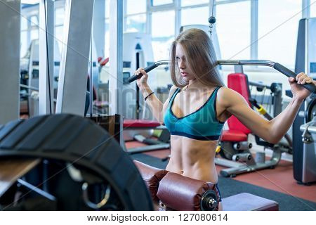 Image of sexy woman exercising on simulator in fitness room