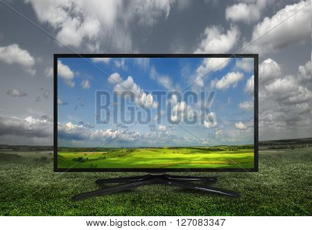Modern television on a green meadow, showing the colors more beautiful than reality