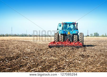 Blue tractor in the field on a sunny day