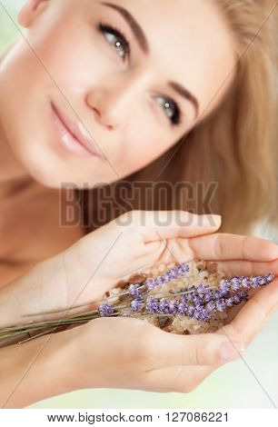 Woman at beauty salon, beautiful female at spa holds lavender flowers and bath salt, aromatherapy herbal anti-stress treatment for health of mind and soul, body skin face and hair care