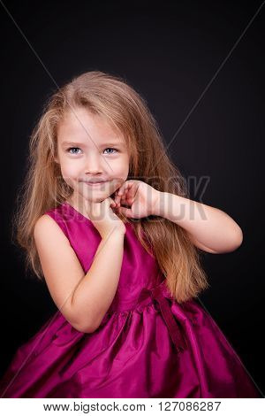 Little cute girl in a pink dress on a black background in the studio