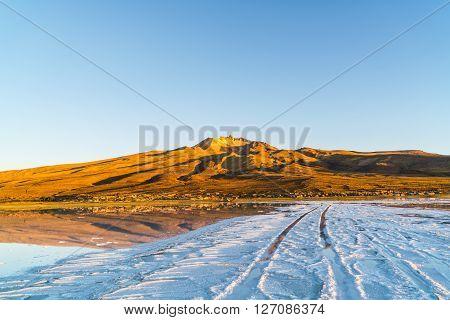 Wheel tracks to Coqueza Village at the salt lake of Solar De Uyuni in Bolivia