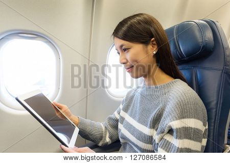 Woman use of digital tablet in aircraft