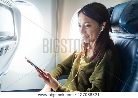 Woman passenger in airplane using cellphone with earphone