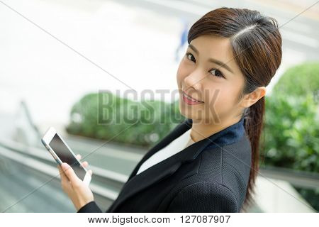Businesswoman use of cellphone and standing at escalator