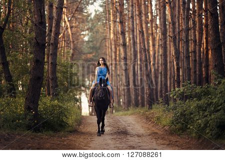 Young beautiful brunette girl in blue dress ride on the black horse in forest