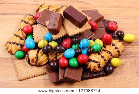 Heap of candies and cookies on wooden table too many sweets concept of unhealthy food and reduction of eating sweets