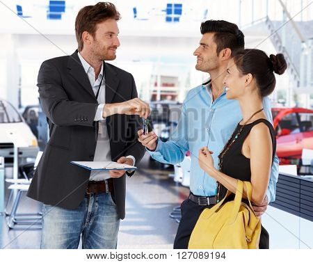 Young couple receiving car keys from agent in car showroom.