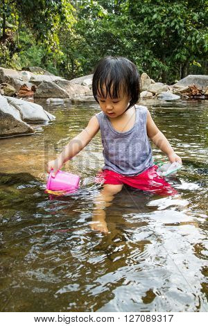 Asian Little Chinese Girl Playing In Creek