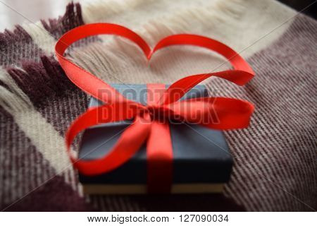Packaged present with red ribbon on plaid