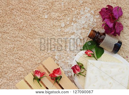 Herbal bathroom spa set, top view. Sea salt, essential oil, flowers, beige terry towel background. ** Note: Visible grain at 100%, best at smaller sizes