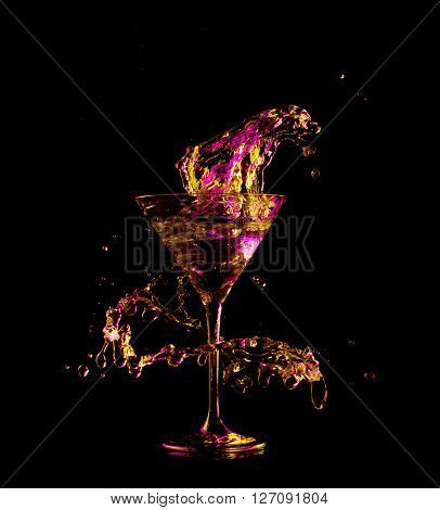 cocktail in glass with splashes on dark background. Party club entertainment. Mixed light