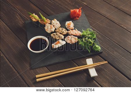 Japanese food restaurant, sushi gunkan roll plate, platter set. Creative food. Set with chopsticks, ginger, soy, wasabi. Sushi at rustic wood background and black stone. POV, horizontal image