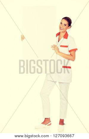 Happy female doctor holding empty banner