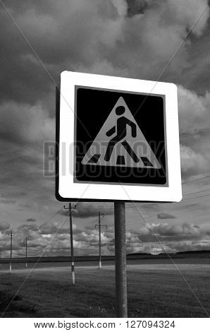 A pedestrian crossing sign on sky background. Photo traffic sign on a metal pole.