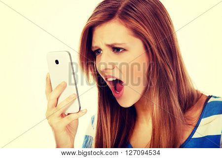 Teenage angry woman screaming into the phone