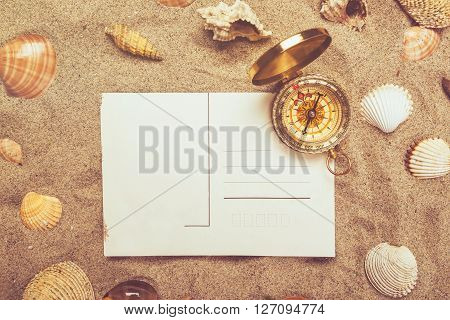 Blank postcard in hot beach sand and magnetic compass with some sea shells copy space for summer holiday vacation message.