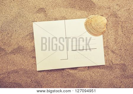 Blank postcard and sea shell in hot beach sand top view of copy space for summer holiday vacation message in a letter retro tone