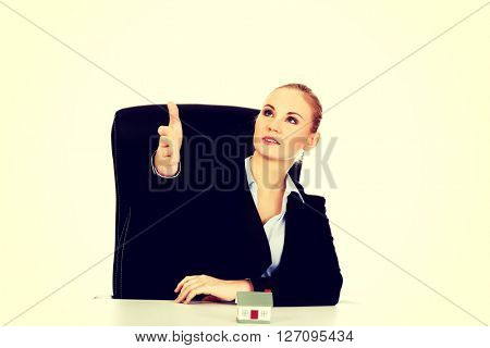 Business woman with an open hand ready for handshake and house model on the desk