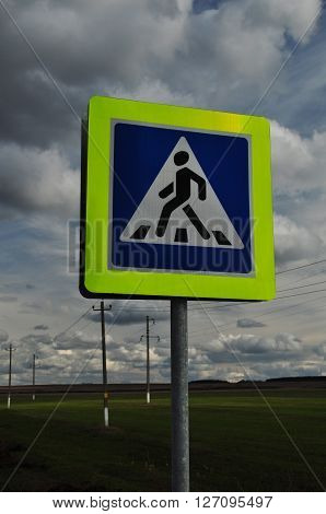 A pedestrian crossing sign. Monochrome photo traffic sign on a metal pole.