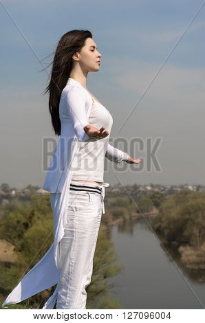 Girl Meditates On A Hill Against The Blue Sky.