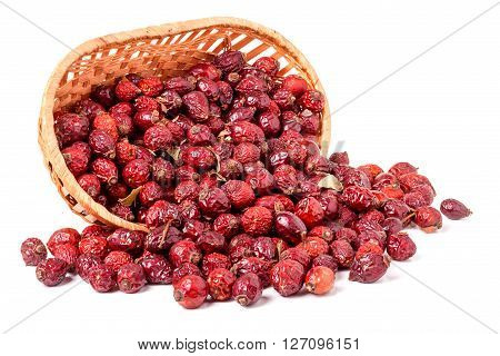 Dried rose hips in a wicker basket isolated on white background.