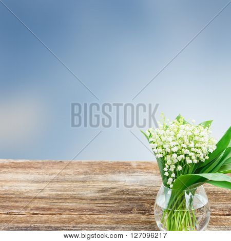 Lilly of valley flowers in glass on wood border on blue background