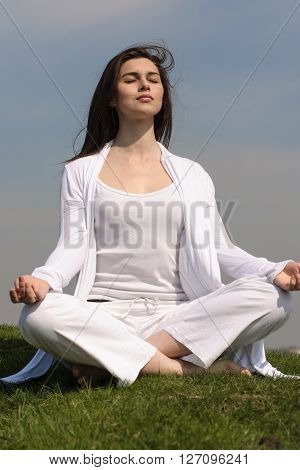 Girl Performs Yoga On The Hill Against The Blue Sky.