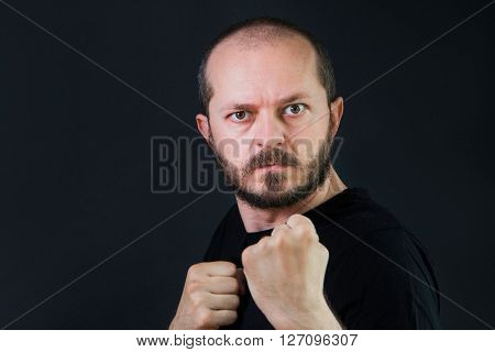 Serious aggressive man with beard and mustaches on black background in low key, holding fists and threatening, ready for fight