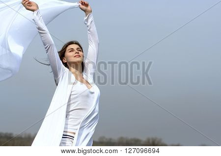 Girl Holds Fabric In Hands Waving In The Wind