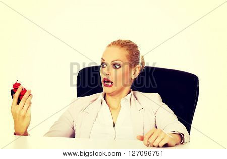 Surprised business woman looking at alarm clock behind the desk