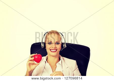 Happy call center woman sitting behind the desk and holding heart model