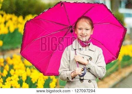 Outdoor portrait of adorable little girl of 7-8 years old, wearing beige trench coat, holding big pink umbrella, standing under the rain in a beautiful park with yellow narcissus
