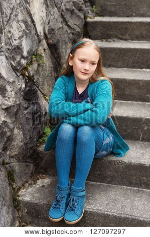 Outdoor fashion portrait of adorable little girl of 8-9 years old, wearing blue clothes and shoes, sitting on stairs in a city
