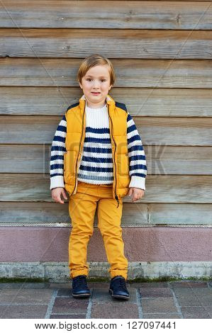 Fashion little boy of 4-5 years old, wearing yellow vest, trousers and white pullover with blue stripes, standing against wooden background
