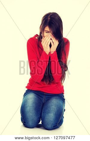 Woman with sinus pain sitting on the floor.